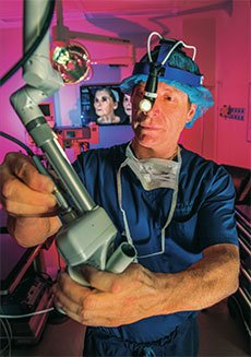 Dr. Miller wearing scrubs working with a machine